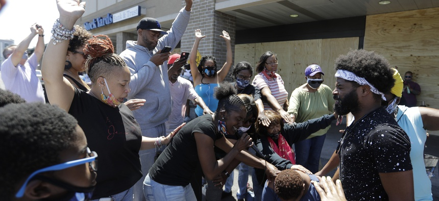 A group prays at the intersection where David McAtee was killed by police.