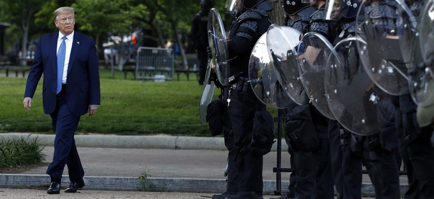 President Donald Trump walks past police in Lafayette Park after he visited outside St. John's Church across from the White House Monday, June 1, 2020, in Washington.