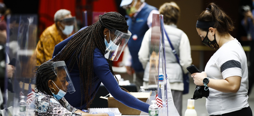 Election workers, left, check in voters before they cast their ballots in the Pennsylvania primary in Philadelphia, Tuesday, June 2, 2020.