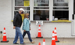 A couple, wearing protective masks due to COVID-19, walk through social distanced cones for patrons as they pass a seaside pizza shop, Monday, June 1, 2020, in Salisbury, Mass.