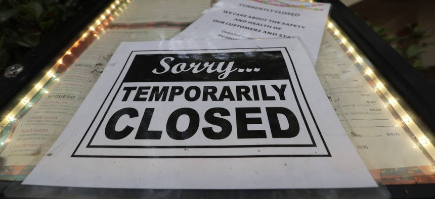 In this April 28, 2020 file photo, a closed sign is posted at a restaurant along the River Walk in San Antonio.