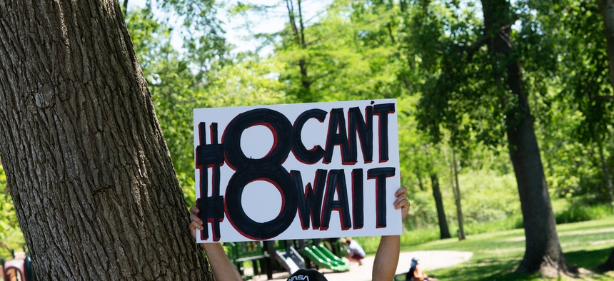 A protester in Michigan holds up a sign for the #8CantWait campaign.