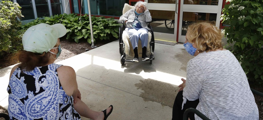 A resident and visitors at the Hebrew Rehabilitation Center, on June 10, 2020, in Boston.