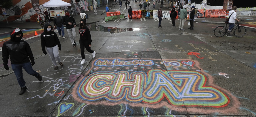 """People walk past street art that reads """"Welcome to CHAZ,"""" Thursday, June 11, 2020, inside what is being called the """"Capitol Hill Autonomous Zone"""" in Seattle."""