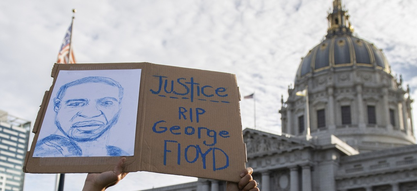 A sign is held up outside of San Francisco City Hall during a protest over the death of George Floyd in police custody.