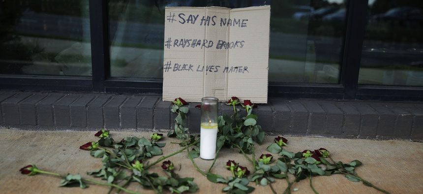 A memorial with roses and a sign is displayed near a sidewalk on Saturday, June 13, 2020, near the Atlanta Wendy's restaurant where Rayshard Brooks was fatally shot by police late Friday.