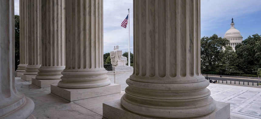 he columns of the Supreme Court are seen with the Capitol at right, in Washington, early Monday, June 15, 2020.