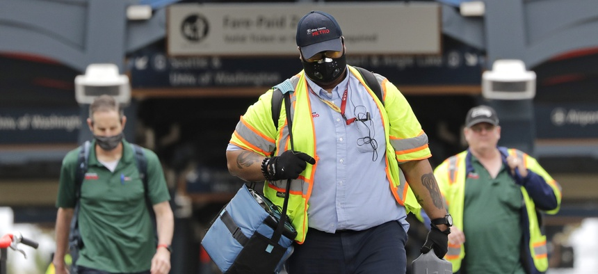 King County Metro bus workers walk off of a transit platform Monday, May 11, 2020, in Seattle.