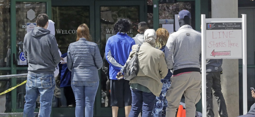 In this April 2020, file photo, people line up outside the Utah Department of Workforce Services in Salt Lake City.