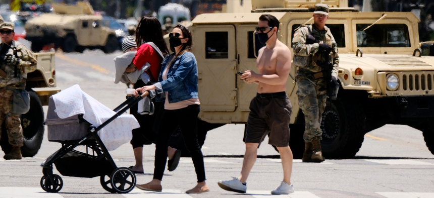 A woman pushes her baby stroller across a blocked street with National Guard in Santa Monica, Calif. on June 7, 2020. Troops had been deployed to California cities to help with the response to protests against police brutality.