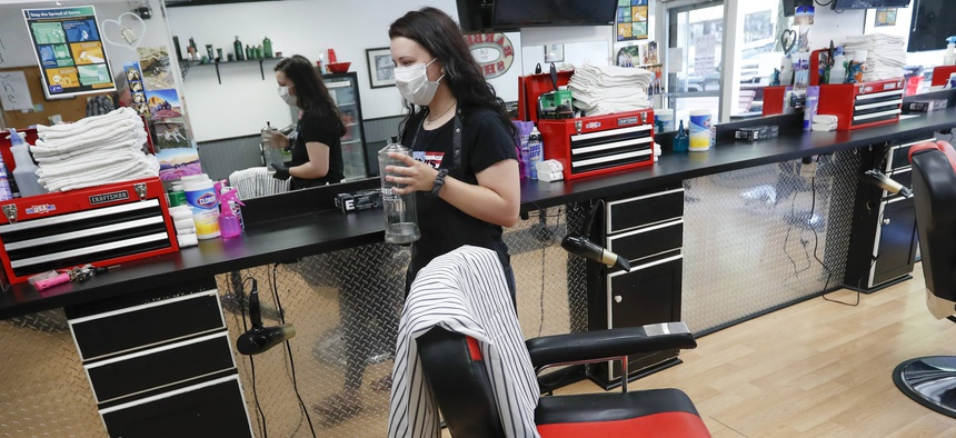 A stylist arranges items in her workspace Thursday, June 4, 2020, as she prepares for her first day back on the job at the West View Barber Shop ahead of Pennsylvania's loosening of Covid-19 restrictions.