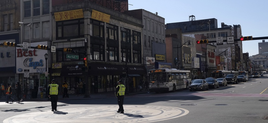Newark police officers, encouraging people to practice social distancing, patrol an intersection in Newark, N.J., Thursday, March 26, 2020.