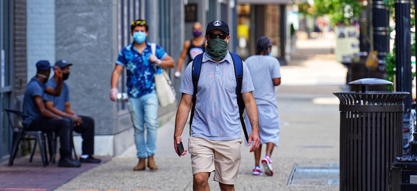 People in Washington, D.C. walk with masks on.