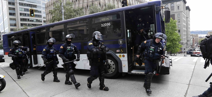 Washington State Police troopers walk off of a bus in front of Seattle City Hall as they prepare for demonstrators to arrive Wednesday, June 3, 2020, in Seattle.