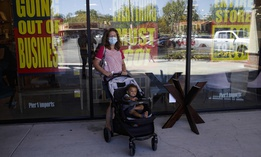 A shopper stands outside of a Pier 1 Imports store as going out of business signs are posted amid the coronavirus pandemic Wednesday, July 1, 2020, in Santa Clarita, Calif.