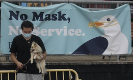 Manny Munoz wears a mask while holding his dog Princess Diana in front of a sign at the Santa Cruz Beach Boardwalk during the coronavirus outbreak in Santa Cruz, Calif., Thursday, July 2, 2020.(AP Photo/Jeff Chiu)