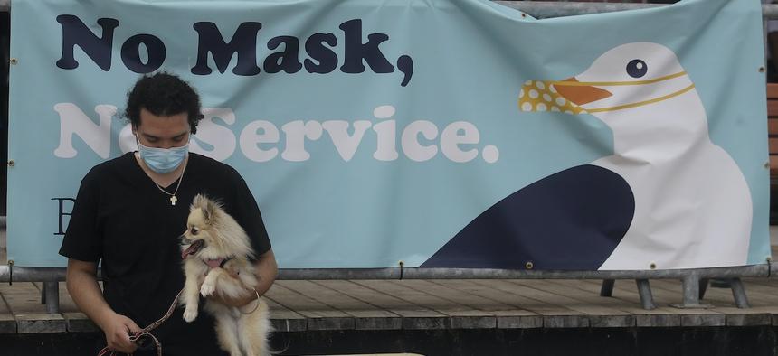 Manny Munoz wears a mask while holding his dog Princess Diana in front of a sign at the Santa Cruz Beach Boardwalk during the coronavirus outbreak in Santa Cruz, Calif., Thursday, July 2, 2020.(AP Photo/Jeff Chiu)