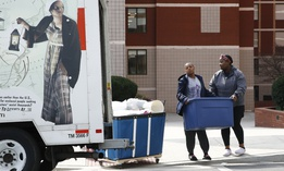 Howard University students Ayana Sallee, left, of Chesapeake, Va., and Jennifer Nnadozie, of Atlanta, load belongings into a U-Haul truck as they move out of their dorm in Washington, Wednesday, March 18, 2020.