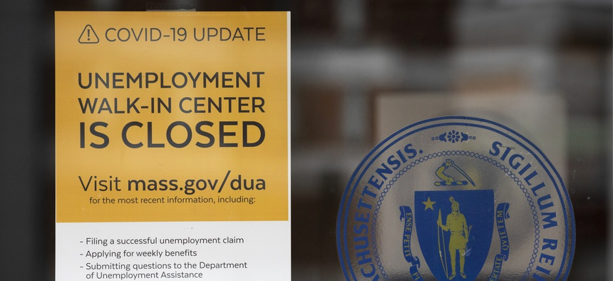 A sign outside of the Massachusetts Unemployment Office. Unemployment claims are severely straining the legacy systems states use to process them.