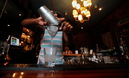A bartender makes cocktails inside Bar Tonique in New Orleans on July 9, 2020. Two days later, Louisiana Gov. John Bel Edwards ordered all bars to close.