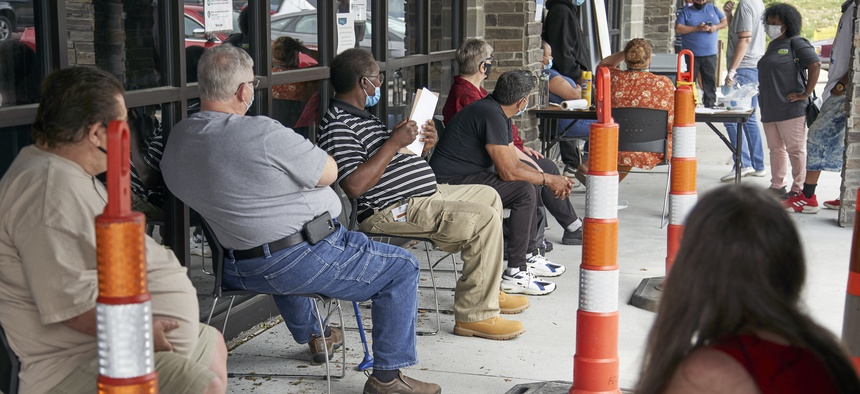 Job seekers exercise social distancing as they wait to be called into the Heartland Workforce Solutions office in Omaha, Neb., Wednesday, July 15, 2020.