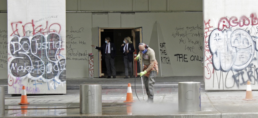 In this July 8, 2020 photo, a worker washes graffiti off the sidewalk in front of the Mark O. Hatfield Federal Courthouse in downtown Portland, Ore., as two agents with the U.S. Marshals Service emerge from the boarded-up main entrance.
