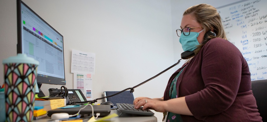 Heather Griggs, operations chief of the Umatilla County Public Health Department COVID-19 contact tracing center in Pendleton, Ore., checks in with public health staff in neighboring Morrow County.