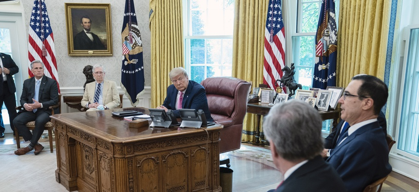 House Minority Leader Kevin McCarthy of Calif., left, speaks during a meeting with Senate Majority Leader Mitch McConnell of Ky., center, and President Donald Trump in the Oval Office of the White House, Monday, July 20, 2020, in Washington.