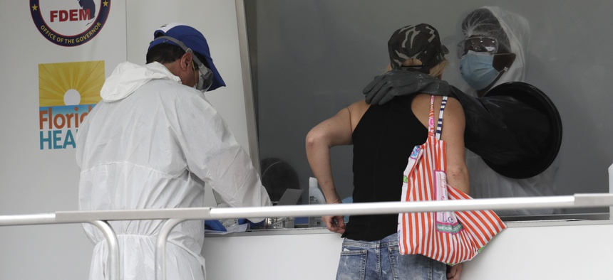 A woman is tested for COVID-19 at a walk-up testing site during the coronavirus pandemic, Friday, July 17, 2020, in Miami Beach, Fla.