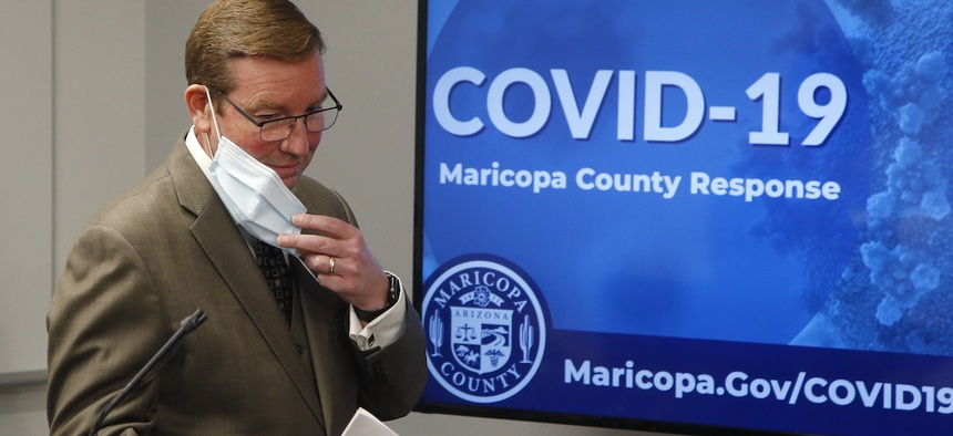 Robert Rowley, director of the Maricopa County Emergency Management Department, removes his face covering as he prepares to speak at a July 16 press conference.