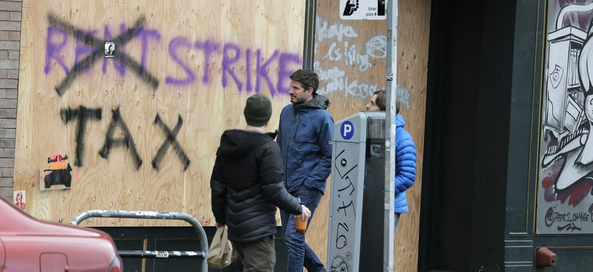 Pedestrians walk past graffiti advocating rent and tax strikes in Seattle.