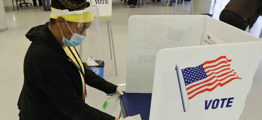Board of elections worker Valerie Tyree cleans an election booth after a person voted in the state's primary election at the Cuyahoga County Board of Elections, Tuesday, April 28, 2020, in Cleveland.