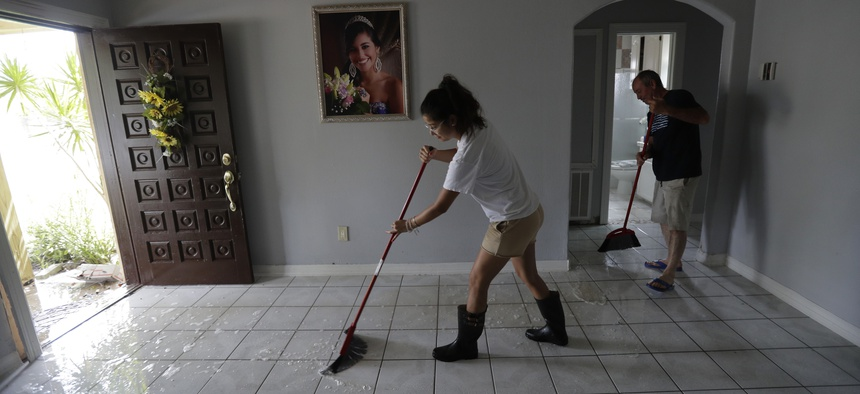 Michelle Garcia, left, and her father Martin, right, sweep water from their home, Monday, July 27, 2020, in Weslaco,Texas. The Garcia's home was flooded by Hurricane Hanna as it passed through the area dropping heavy rains which caused flooding.
