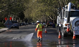 A city utility worker washes down a street in Sacramento, California in March 2020.
