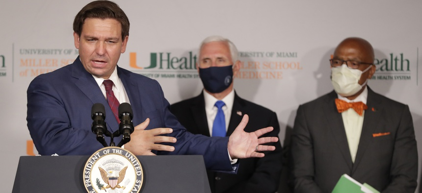 Florida Gov. Ron DeSantis, left, speaks during a news conference as Vice President Mike Pence and Henri Ford, right, dean of the University of Miami Leonard M. Miller School of Medicine.